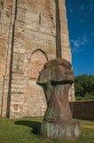 La grande statue de deux a moulé des têtes dans le jardin des ruines médiévales d'église sous le ciel bleu ensoleillé chez Damme Photo libre de droits