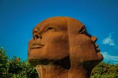 La grande statue de deux a moulé des têtes dans un jardin sous le ciel bleu ensoleillé chez Damme Images stock