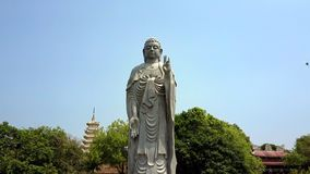 La grande statue grise de Bouddha se tient contre le ciel bleu de pagoda banque de vidéos