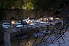 La grande table rustique s'est préparée à un dîner extérieur la nuit Images libres de droits
