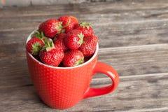 La grande tazza rossa ha riempito di fragole rosse mature fresche succose succulenti su un vecchio piano d'appoggio strutturato d Immagine Stock
