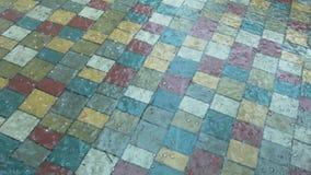 La grandine e la pioggia cadono sulla lastra per pavimentazione colorata archivi video