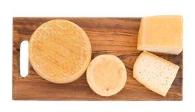 La granja produjo los quesos orgánicos en el tablero de madera, aislado en blanco Fotografía de archivo libre de regalías