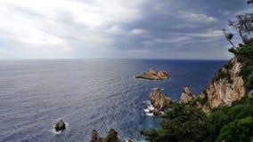 La Grecia, Corfù: Rocce e mare intorno al ` animatore della primavera del ` del monastero Immagini Stock