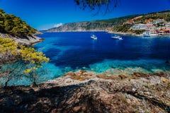 La Grecia di stupore, barche a vela bianche in baia blu del villaggio variopinto pittoresco Asso in Kefalonia immagine stock libera da diritti