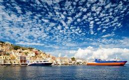 La Grecia Dodecanesse Isola Symi Simi Case variopinte sulle rocce Grande nave passeggeri due al pilastro Immagine Stock Libera da Diritti