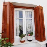 La Grecia, finestra della casa e vasi da fiori Immagine Stock