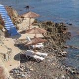La Grecia, scale blu alla spiaggia tranquilla con gli ombrelli e le sedie Immagini Stock