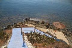 La Grecia, scale blu alla spiaggia tranquilla con gli ombrelli e le sedie Immagine Stock Libera da Diritti