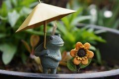La grenouille avec le parapluie et une fleur regardent hors du pot de fleur Photos libres de droits