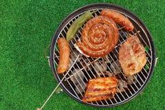 La griglia del barbecue con i vari generi di carne, fa un picnic Concep all'aperto Immagine Stock