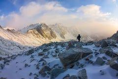 La grimpeuse de femme dans le casque et vers le bas veste avec des bâtons de trekking s'attaque vers le haut à l'aube Photo libre de droits