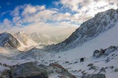 La grimpeuse de femme dans le casque et vers le bas veste avec des bâtons de trekking s'attaque vers le haut à l'aube Image libre de droits