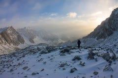 La grimpeuse de femme dans le casque et vers le bas veste avec des bâtons de trekking s'attaque vers le haut à l'aube Photos stock