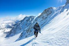 La grimpeuse de femme dans le casque et vers le bas veste avec des bâtons de trekking s'attaque vers le haut à l'aube Photo stock