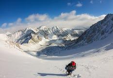 La grimpeuse de femme dans le casque et vers le bas veste avec des bâtons de trekking s'attaque vers le haut à l'aube Photographie stock