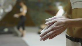 La grimpeuse de femme marque des mains à la craie avec la poudre blanche de craie avant montée dans le gymnase s'élevant d'intéri clips vidéos