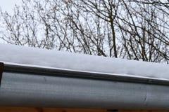 La grondaia sul tetto della neve Fotografie Stock Libere da Diritti