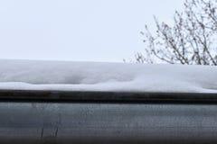 La grondaia sul tetto della neve Immagine Stock Libera da Diritti