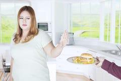 La grosse femme rejette la nourriture malsaine photos libres de droits
