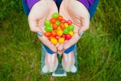 La grosse femme veut perdre des prises de poids en petites sucreries colorées de bateau pliées par mains photos stock