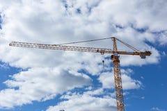 La gru alta sul cantiere si appanna il cielo blu Fotografie Stock Libere da Diritti
