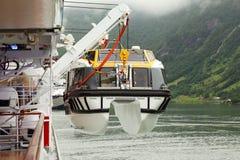 La gru alza la barca di passeggeri alla grande fodera Fotografia Stock