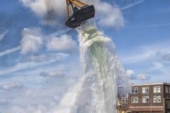 La gru a benna di una gru getta l'acqua nel mare fotografia stock