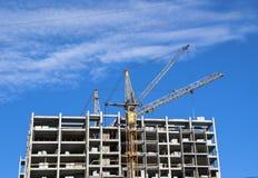 La gru della costruzione sta costruendo l'alta costruzione Fotografia Stock