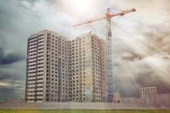 La gru di costruzione costruisce la casa residenziale dell'multi-appartamento Fotografia Stock