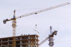 La gru di costruzione fornisce ai lavoratori i materiali per la costruzione che un nuovo palazzo multipiano alloggia Fotografia Stock Libera da Diritti