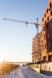 La gru a torre e la nuova costruzione di mattone rosso sta costruenda Giorno soleggiato di inverno Fotografia Stock