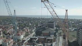 La gru a torre funziona al mare per la costruzione dell'hotel stock footage