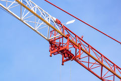 La gru a torre rossa della costruzione su cielo blu con bianco si appanna il fondo, dettaglio Immagini Stock