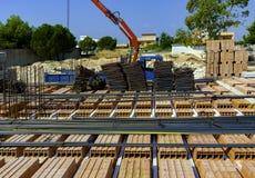 La grue a arrangé des matériaux de construction de barres d'acier, image stock