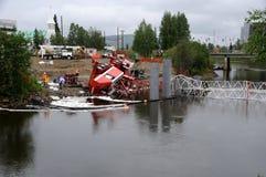 La grue de construction de passerelle culbute dans le fleuve Image stock