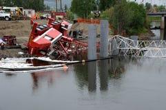 La grue de construction de passerelle culbute dans le fleuve Photo stock