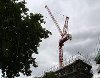 La grue de construction domine sur le ciel nuageux avec un certain fond photographie stock