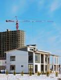 La grue de construction et le bâtiment contre le ciel bleu Images libres de droits