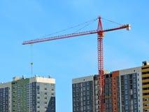 La grue de construction et le bâtiment contre le ciel bleu Photographie stock libre de droits