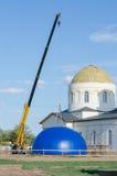 La grue soulève le dôme de l'église reconstruite de la mère de Kazan de Dieu dans le village Solodniki Images libres de droits