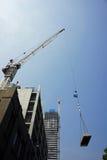 La grue sur le chantier de construction soulève des matériaux Photographie stock libre de droits
