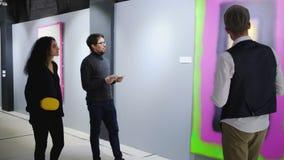La guía masculina está hablando para dos visitantes de la galería de arte y está mostrando imágenes metrajes