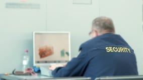 La guardia all'aeroporto controlla le borse sui raggi x Un uomo esamina con attenzione lo schermo del sistema di sicurezza stock footage
