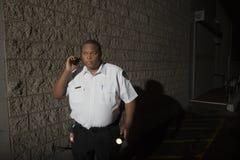 La guardia giurata With Walkie Talkie e la torcia sorveglia alla notte Fotografie Stock Libere da Diritti