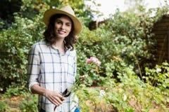 La guarnizione della donna fiorisce con i tagli della potatura in giardino un giorno soleggiato Fotografia Stock Libera da Diritti
