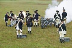 La guerra revolucionaria re-enactors reconstruye el fuego de cañón y el alto el fuego subsiguiente del ejército británico, en qui Imagen de archivo libre de regalías