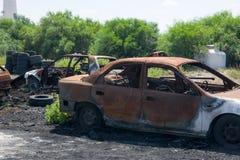 La guerre signe la voiture abandonnée brûlée après bombardement de la ville Images stock