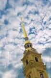 La guglia del Peter e di Paul Fortress contro lo sfondo del cielo nuvoloso immagini stock libere da diritti