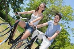 La guida adolescente delle coppie del ritratto all'aperto va in bicicletta in natura Fotografie Stock